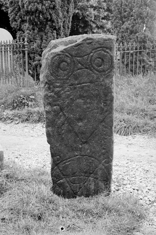 Pictish symbol stone standing in kirkyard. View of face, showing double-disc and Z-rod, and two crescent and V-rods. Half-plate glass negative.