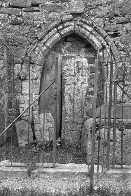 View of sculptured stones and arched doorway in railed enclosure. Original negative captioned: 'Sculptured Cross Stones, Old Church of Tullich near Ballater July 1902'.