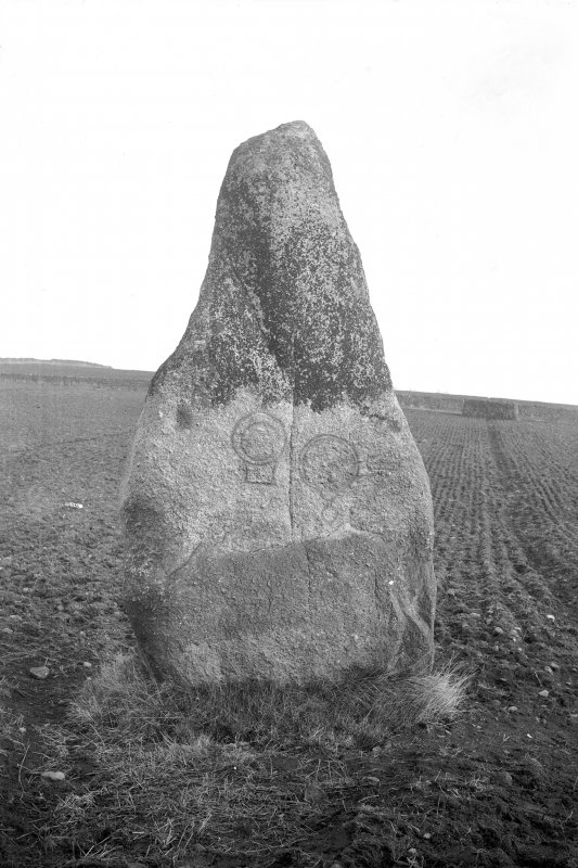 View of standing stone, bearing comb, mirror, and mirror-case symbols. Original negative captioned: 'Sculptured Stone at Nether Corskie near Waterton of Echt Feb 1914'.