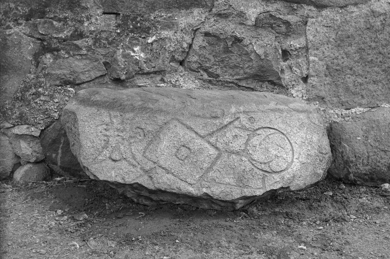View of Pictish symbol stone lying on its side against a stone wall. Original negatives captioned: 'Sculptured Stone at Newton of Lewesk, Rayne July 1915'.