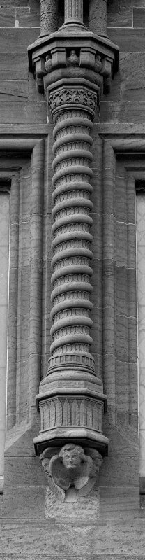 Detail of corbelled-out column above E entrance.