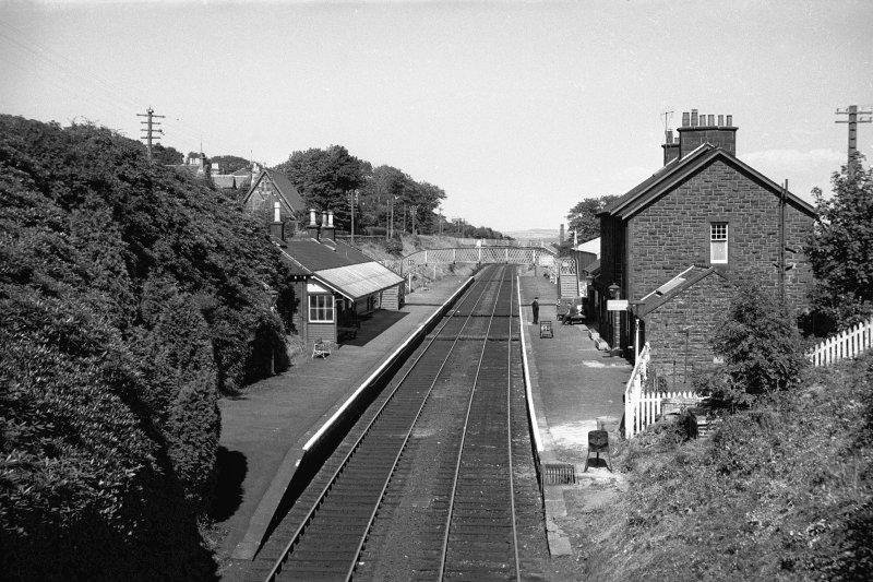 View looking ENE along track with up platform building on left, down platform building on right and footbridge in background