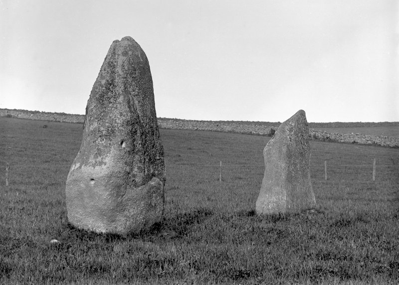 View of two standing stones. Original negative captioned: 'Remains of Stone Circle with 2 cup marks, Nether Corskie 1904'.