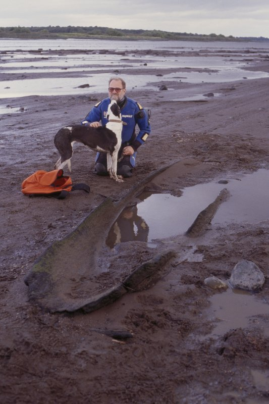The abraded remains of a prehistoric logboat (NO21NW 161), preserved in the esturine sand and mud  were discoverd at Carpow Bank in 2001. View of logboat with Bob Mowat and dog.