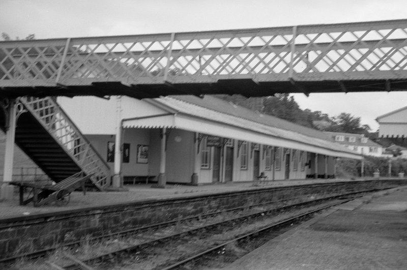 View from W showing SSW front of up platform building with part of footbridge in foreground