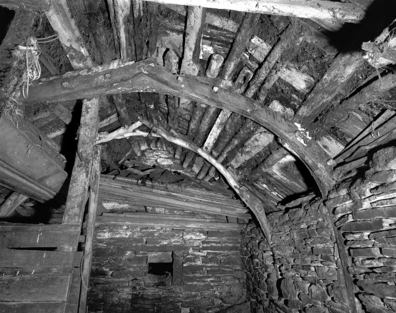 Interior of cruck-framed byre showing roof detail, roof groundwork and cruck-frame in foreground composed of re-used ships timbers; The Buaile, Ramscraigs.