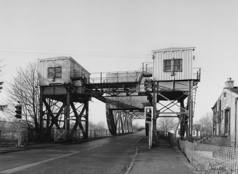 General view from E of E end of bridge, showing two towers supporting control cabins (with connecting overhead gantry) and in centre, rolling/lifting span