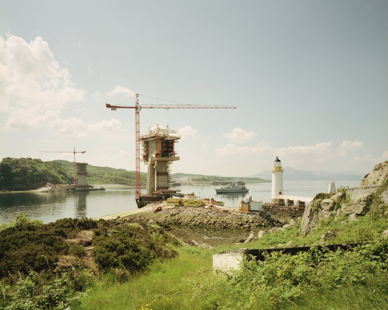 Skye Bridge under construction. View from North-East on the island of Eilean Ban of the North and South piers, Kyleakin Lighthouse (NG72NW 6), and visiting naval vessel passing through.