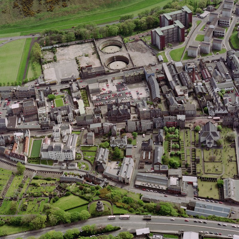 Oblique aerial view showing Canongate area, centred on Holyrood Brewery and showing Canongate Parish Church.