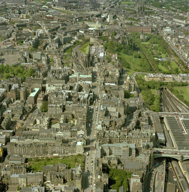 Oblique aerial view of centre of Edinburgh with the High Street running top to bottom across photograph and North and South Bridges running left to right. Digital image of A/40710/CN.