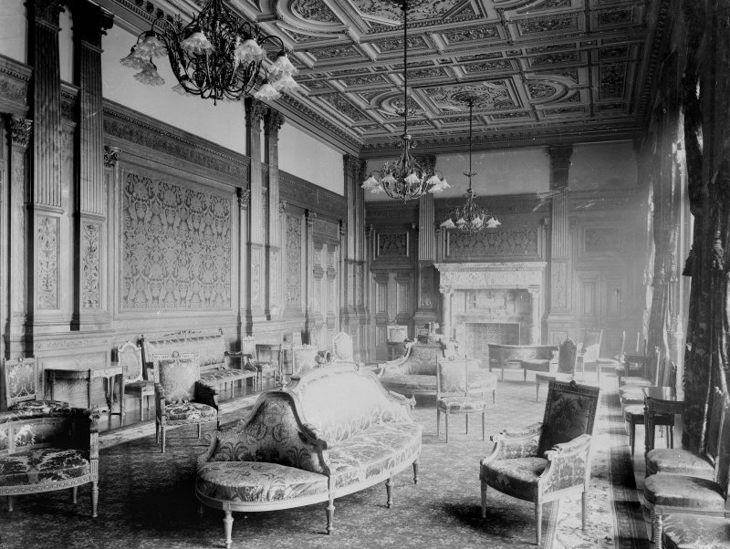 Interior-general view of drawing room with sofas and chairs, also showing patterned wallpaper and marble fireplace