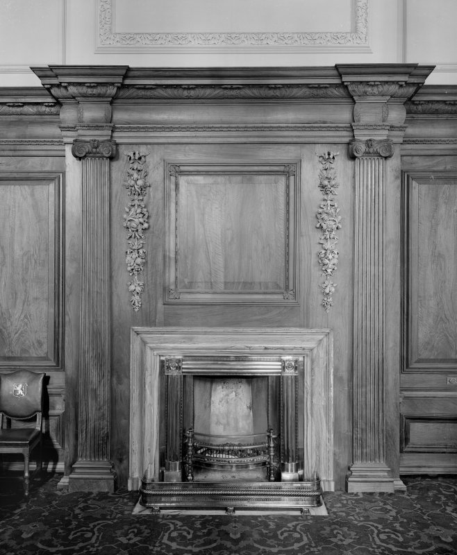 Detail of carved fireplace flanked by carved wooden corinthian pilasters.