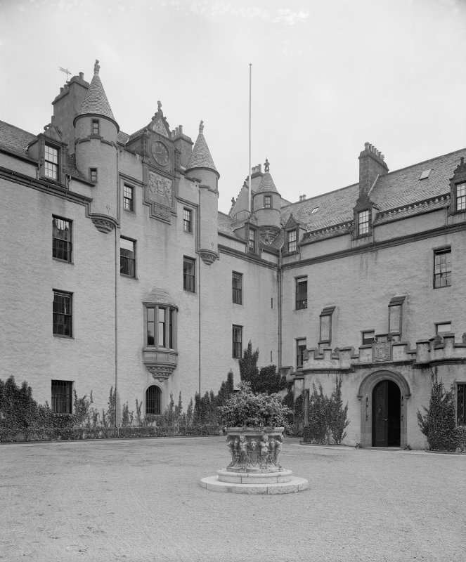 General view of courtyard with carved planter in foreground.