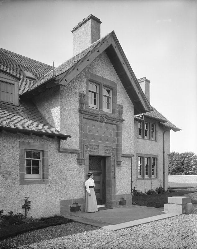 View of entrance doorway with woman standing to left of door, also showing inscription above door reading 'Welcome the Coming and Speed the Parting Guest'