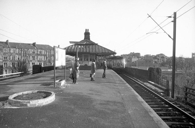 View from NW showing front of Pollokshaws East Station, Glasgow, with tenements behind.