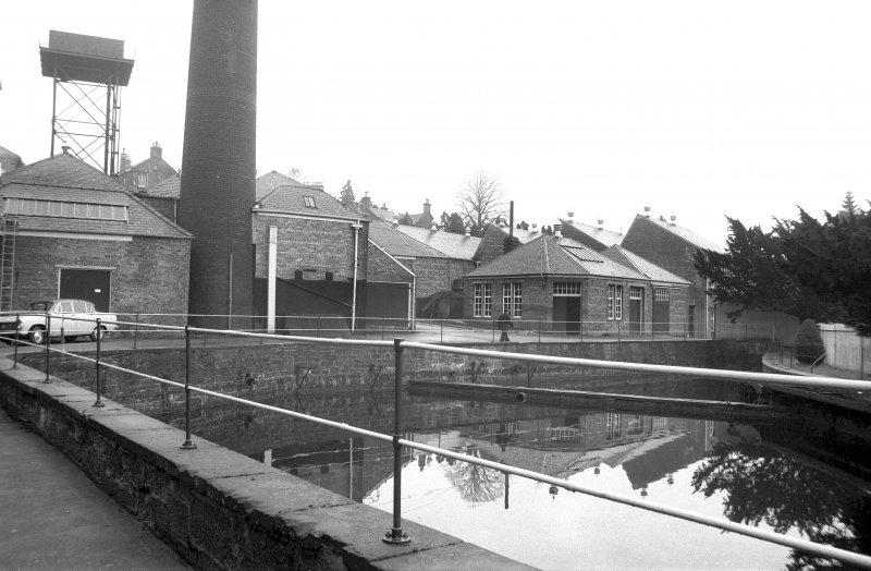 View from SSW showing cooling pond with base of chimney and part of works in background