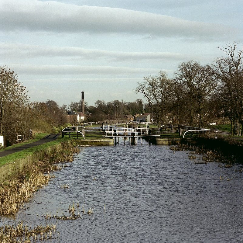 General view of canal, series of locks and distillery from bridge to south west