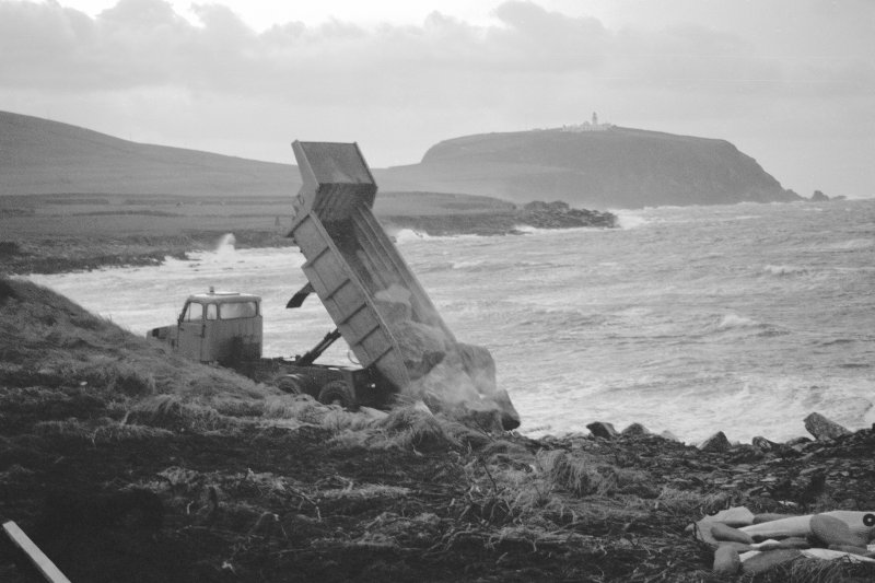 Photograph taken during coastal restorative work to build a breakwater for the future protection of Jarlshof. Foundations for wall W-E. Digital image of C/79128.