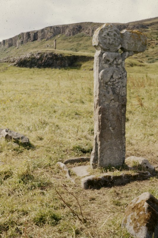 Copy of colour slide showing view of cross shaft in St. Columba's graveyard, A'Chill, Canna with standing stone behind  NMRS Survey of Private Collection  Digital Image Only