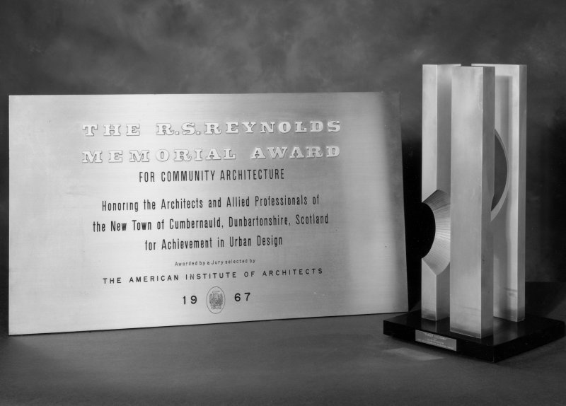View of the R S Reynolds Memorial award plaque and sculpture 'Three Columns' by Roy Gussow. Awarded to Cumbernauld New Town in 1967 for Community Architecture by a jury selected by The American Institute of Architects. Digital image of D 7264.