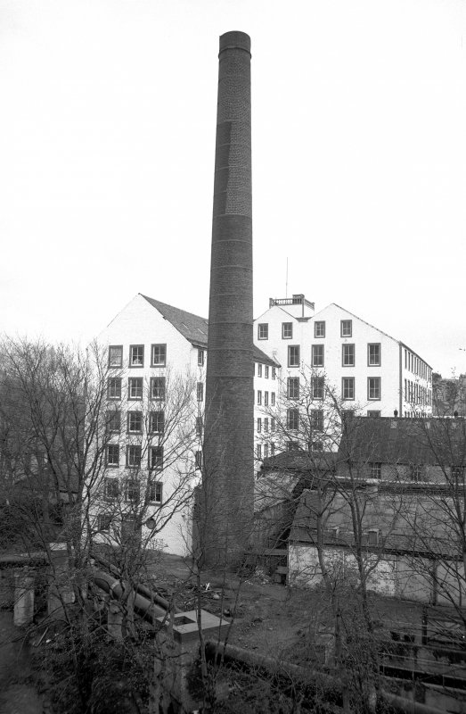 View from WNW showing chimney with part of 'Old End' on left, part of newer block in background and part of outbuildings on right