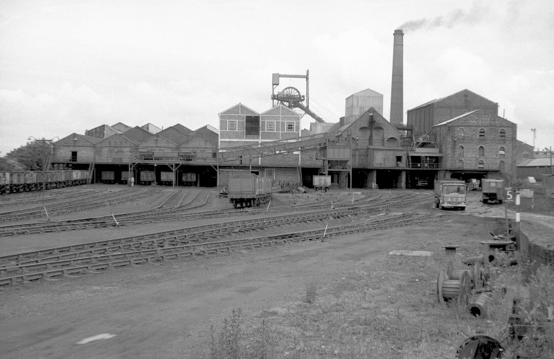 General view from S showing S front of old washer plant (right) with coal elevator shed and hopper, headgear, dense medium plant, pithead building and south elevator conveyor system on left