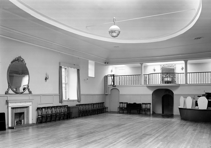 Interior-general view of St Cecilia's Hall, Edinburgh, showing gallery and large oval mirror over fireplace.