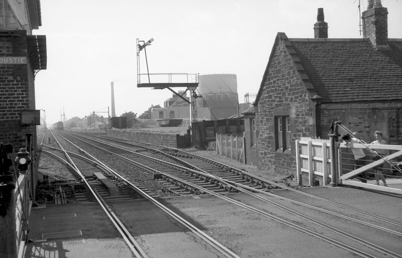 View looking W showing SSE fronts of original station building with level crossing in foreground