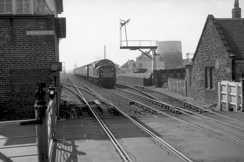 View looking W showing train approaching with original station building on right and level crossing in foreground