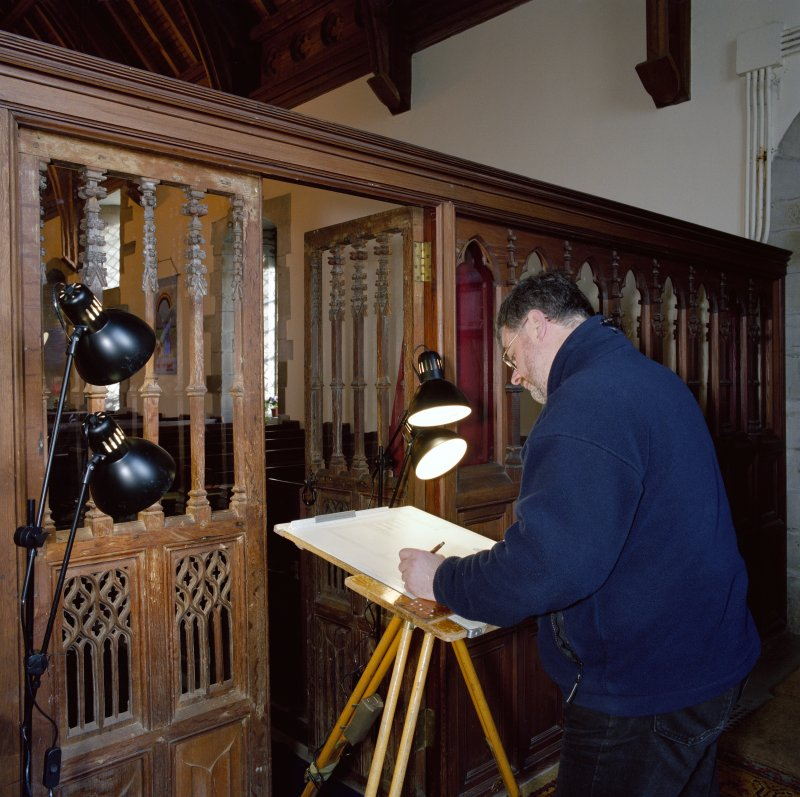 Interior.  View of John Borland (Survey and Graphics) drawing traceried doors in rood screen. Digital copy of E 26558 CN.