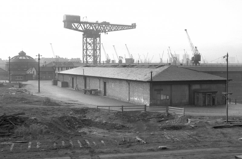 View from NE showing NNE and ESE fronts of E goods shed with crane in background