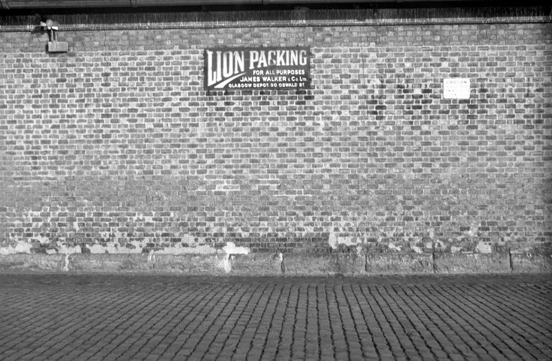 View of S (possible) goods shed showing enamel sign which is inscribed 'LION PACKING FOR ALL PURPOSES JAMES WALKER & CO LTD GLASGOW DEPOT 50 OSWALD ST'