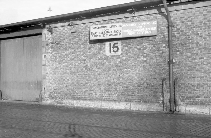 View of goods shed showing sign which is inscribed 'CONSTANTINE LINES LTD FOR MARSSILLES. ITALY. SICILY APPLY to 120 ST VINCENT ST.' and 'SAGUENANY SHIPPING LTD FOR TRINIDAD. BARBADOS. DEMERARA PHONE CITY 6171'