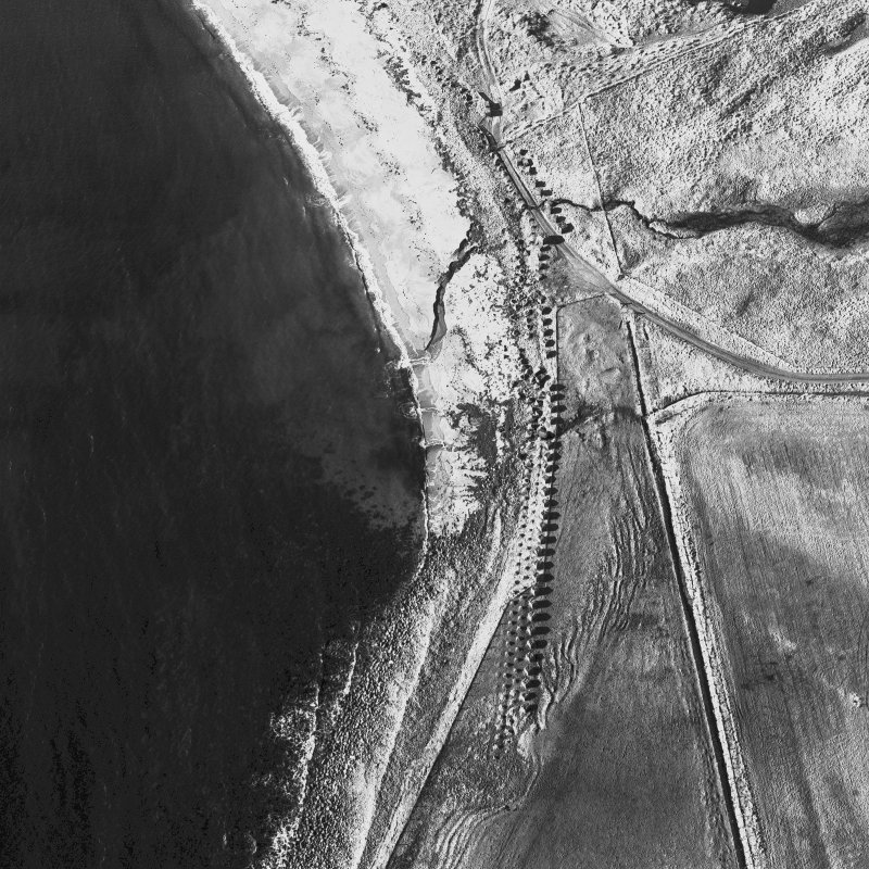 Digital image of E13652, oblique aerial view of Freswick Bay centred on the remains of anti-tank blocks and a road block, taken from the NE.