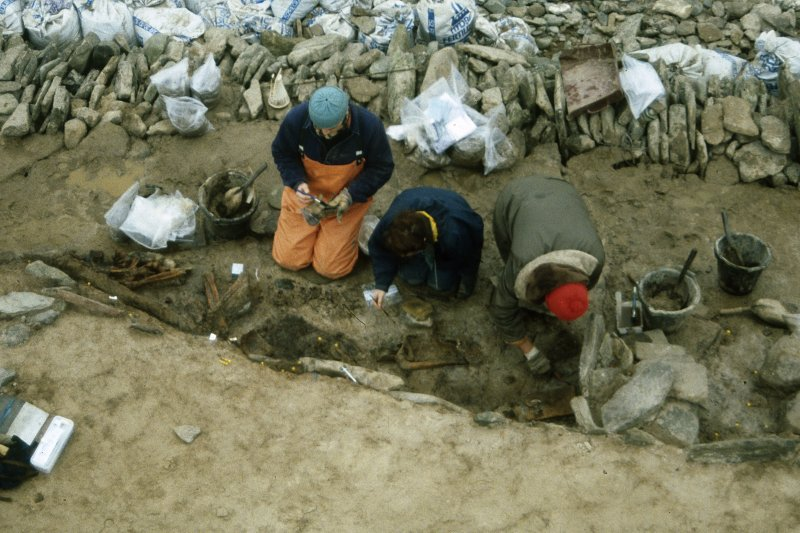 Excavating the boat burial. The skeletons and the whalebone plaque are visible.