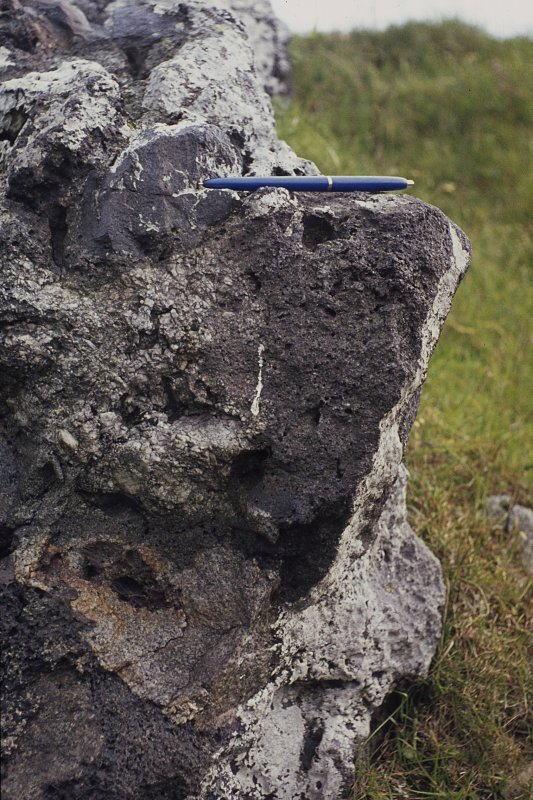 "Copy of colour slide showing possible vitrification near Dunnideer. Insc: "" Detail of vitrification at N.E. corner, outer side - break up of ?granite block and small wood casts in apparently solid bou ..."