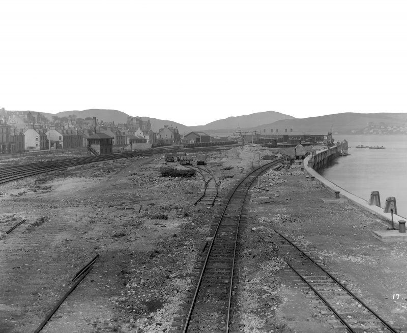 General view of tracks by riverside looking towards station
