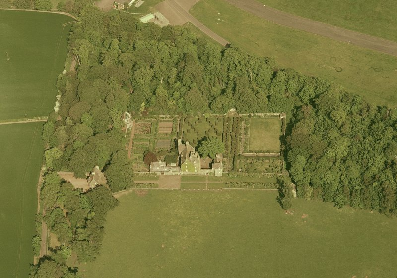 Oblique aerial view of Earlshall country house, formal garden and dovecot, taken from the W. Scanned image of D 5946 CN.