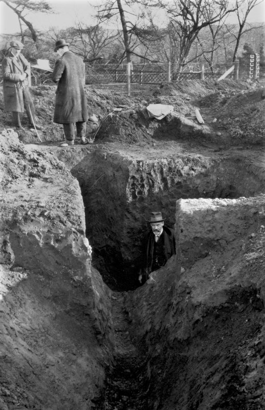 Photograph of second Antonine ditch at Mumrills Roman Fort showing Sir George MacDonald in earlier deeper ditch coalescing with it. Copied from A O Curle photograph album MS/28/461.