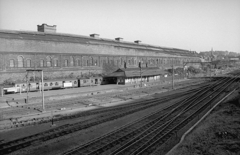 View from NNW showing WNW and NNE fronts of station building with part of tram depot in background