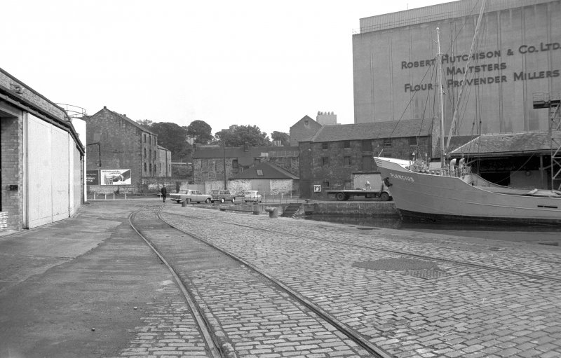 View from SSW showing part of boat in harbour with part of warehouse on left, part of grain wharf warehouses on right and part of grain silo in background