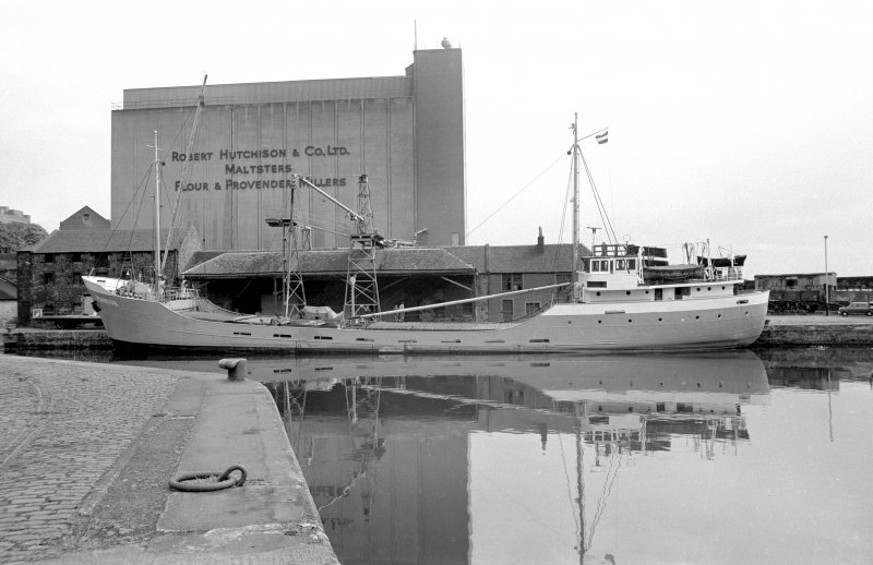 View from SW showing boat in harbour with part of grain wharf warehouses behind and grain silo in background