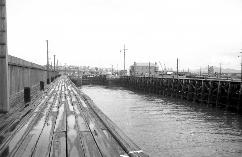 View looking NE along entrance channel of numbers 1 and 2 docks with part of W pier of wave basin on right and dock gate on left