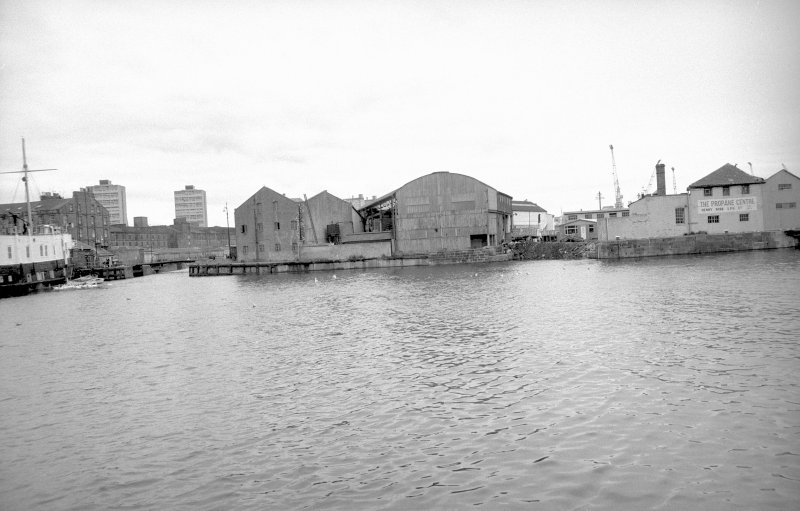General view looking W showing warehouse with entrance to dock on left and engineering works on right