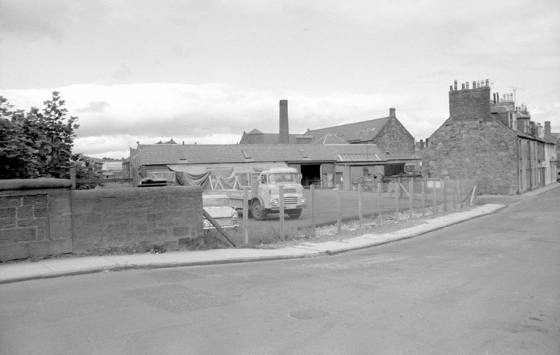 View from S showing part of SSE front of north-light weaving sheds of mill, with numbers 45-37 Panmure Street on right.
