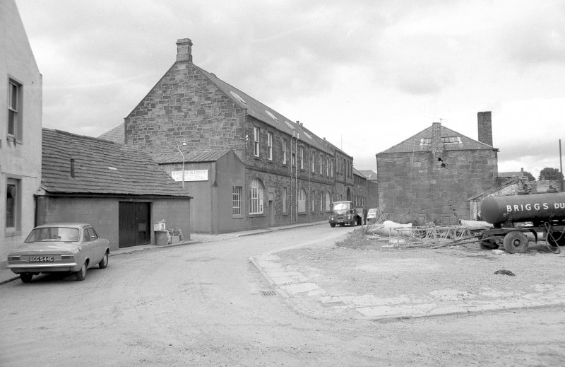 View from SE showing part of SSE and ENE fronts of mill with workshop on right and part of public house on left.