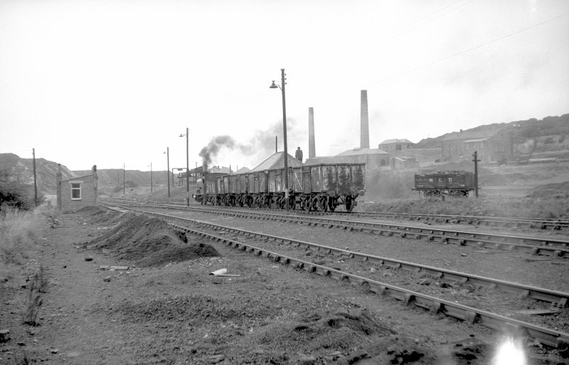 View from SE showing NCB locomotive and wagons near washery with brickworks in background