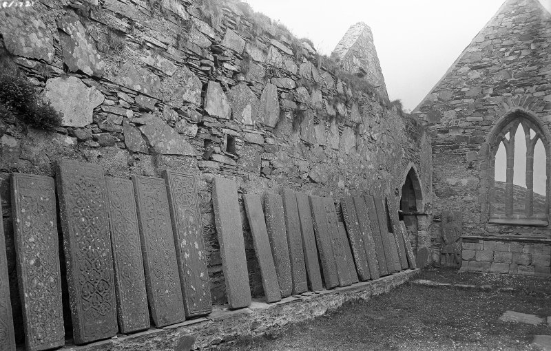 Oronsay Priory, interior, from the west. View of grave-slab lined up along wall.