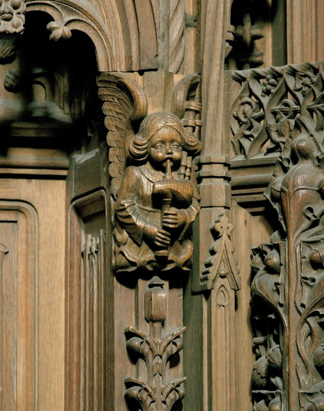 Detail of carved angel playing bag-pipes, to east of main doorway, Thistle Chapel, Edinburgh.