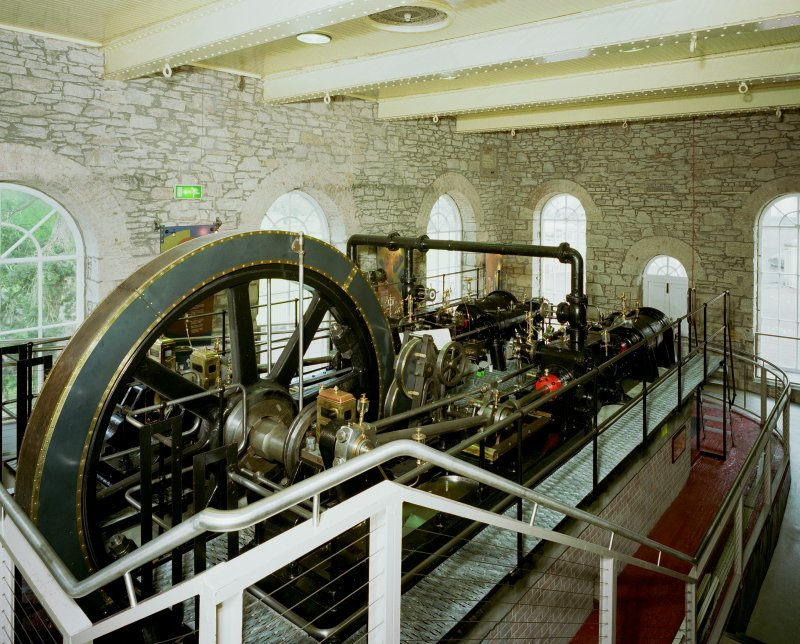 New Lanark: interior. View from S within engine house showing steam engine.  Similar to the original engine, this is a 250hp twin-tandem compound mill engine by Petrie of Rochdale (1912) re-located from Philiphaugh Mill near Selkirk by the New Lanark Conservation Trust